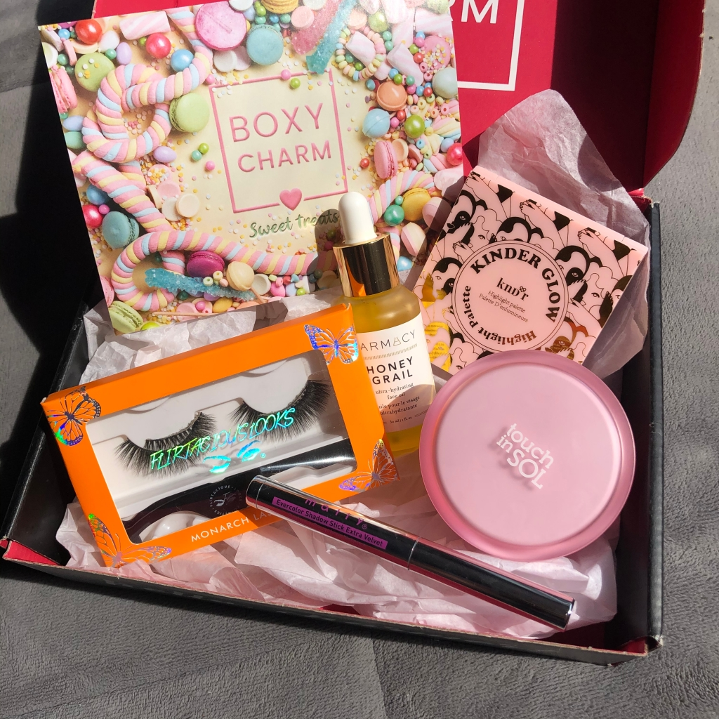 On of the variations of Boxycharm's April box, a beauty subscription service. Products include a pair of Flirtacious lashes, Mally Beauty eyeshadow stick, Touch in Sol face primer, Farmacy face oil and KNDR highlight palette.