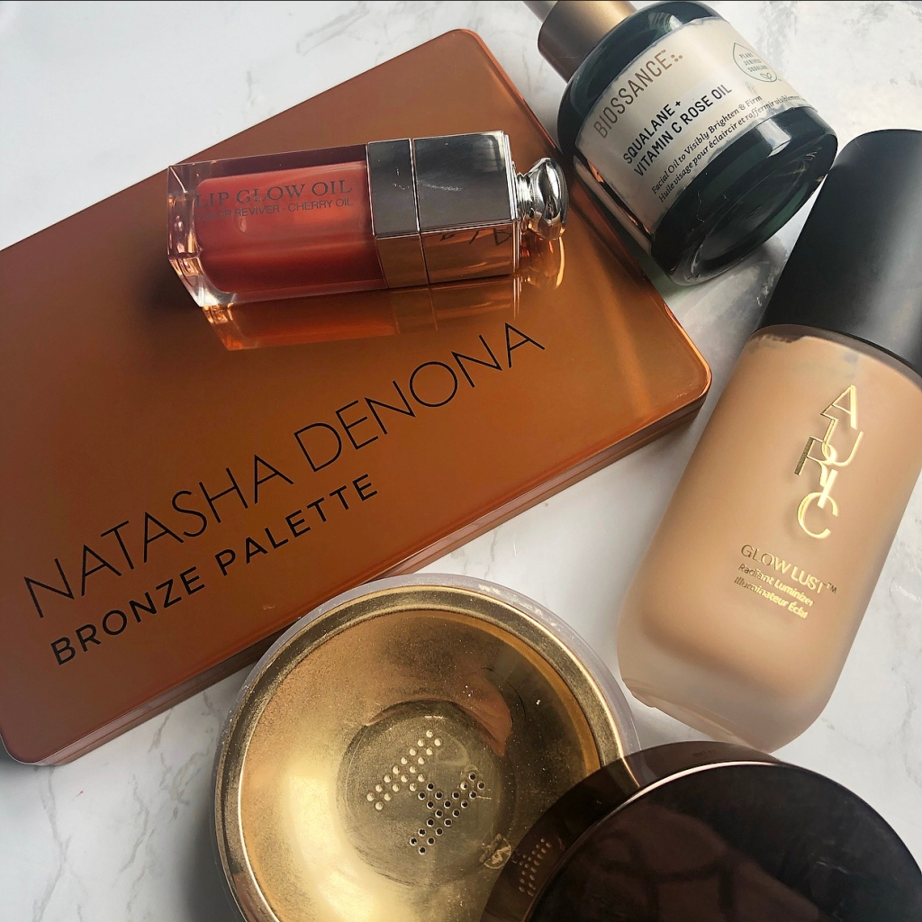 A collection of luxury makeup products including: Natasha Denona Bronze Palette, Dior Lip Glow Oil, Biossance Squalene + Vitamin C Rose Oil, Auric Glow Lust and Hourglass Veil Translucent Setting Powder.